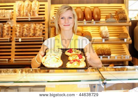 Shopkeeper In Baker Shop With Tablet Full Of Cake