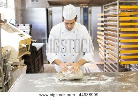 Baker Kneading Dough In Bakery