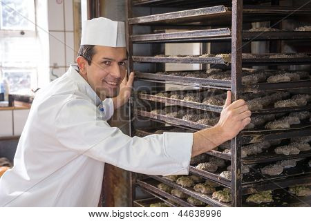 Baker Putting A Rack Of Bread Into Oven