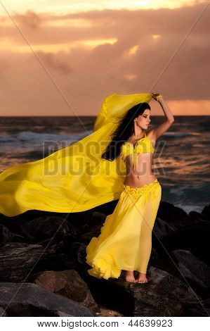 Belly Dancer in Yellow Costume on the Beach at Sunrise