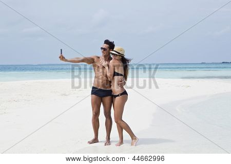 Couple taking a picture of themselves on the beach