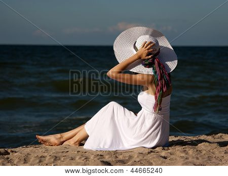 Young Beautiful Woman In A White Dress On The Beach