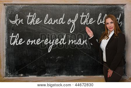 Teacher Showing In The Land Of The Blind, The One-eyed Man Is King On Blackboard