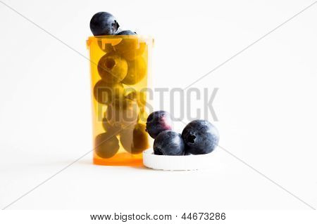Alternative health concept, pill container with blueberries