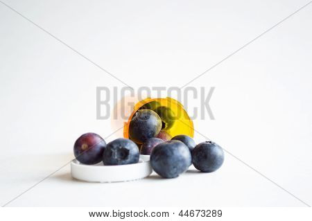 Alternative health concept, pills and blueberries