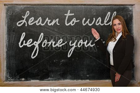 Teacher Showing Learn To Walk Before You Run On Blackboard