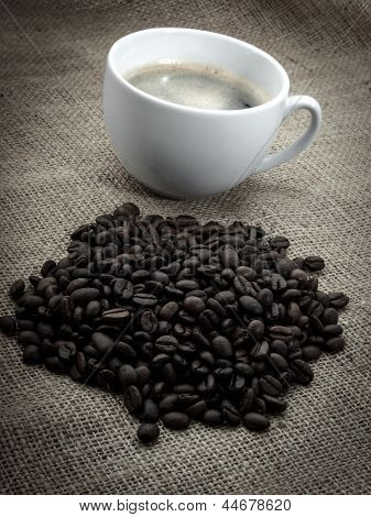 Black Coffee Bean With Coffee Cup, Over Old Burlap Background