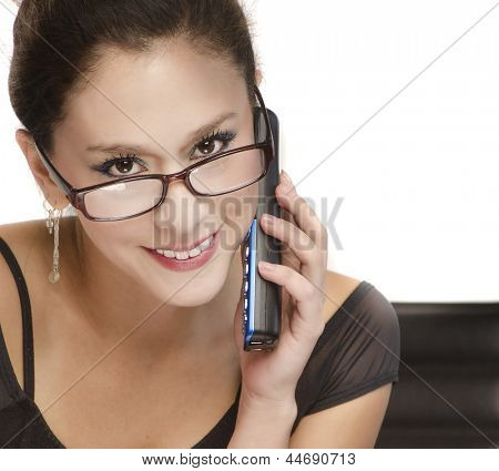 Attractive woman wearing glasses with friendly expression holding talking on phone while sitting at desk.