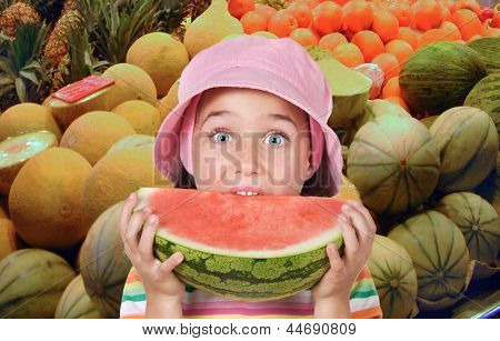 Adorable girl eating watermelon in the greengrocers