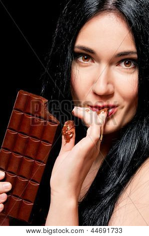 Beautiful young woman with black hair holding a chocolate bar
