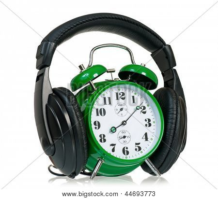 Green alarm clock with headphones, isolated on white background