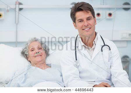 Doctor sitting on the bed next to a patient in hospital ward