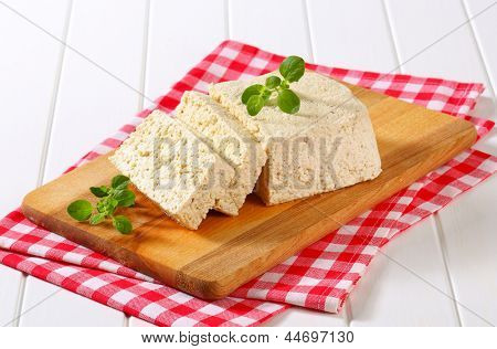 slice block of natural tofu on a wooden cutting board