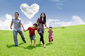stock photo of stroll  - Happy asian family is having a stroll in the park under heart shape clouds - JPG