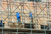 picture of asheville  - Two men stand on scaffolding and work on exterior repairs on the City Building in downtown Asheville North Carolina - JPG