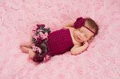 image of headband  - An overhead view of a sleeping newborn baby girl wearing a maroon crocheted headband and romper - JPG