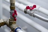 stock photo of furnace  - Pipes and valves of a heating system - JPG