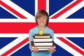 Постер, плакат: Счастливый мальчик проведение стопку книг с Apple против британского флага