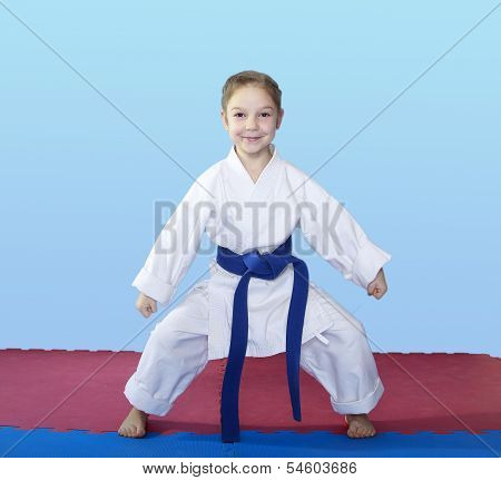 Girl athlete stands in rack of karate