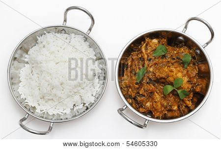 Methi murgh - chicken cooked with fresh fenugreek leaves - in a kadai, or karahi, traditional Indian wok, over white, garnished with fenugreek leaves and seen from above next to a bowl of basmati rice