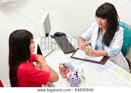 Patient consulting her teet problem with the dentist in dental clinic