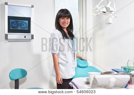 Young Asian female dentist in the clinic looking to camera