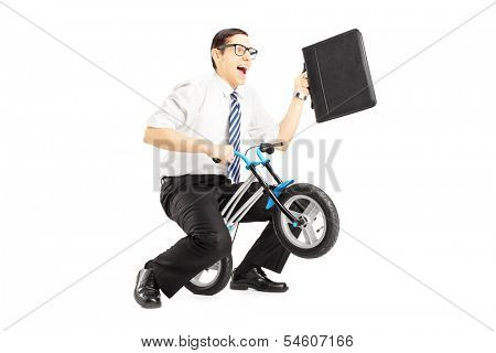 Excited young businessman with leather suitcase riding a small bicycle isolated against white background