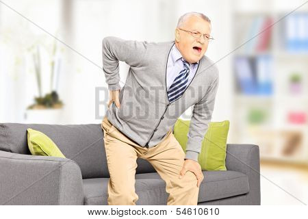 Senior man suffering from back pain at home