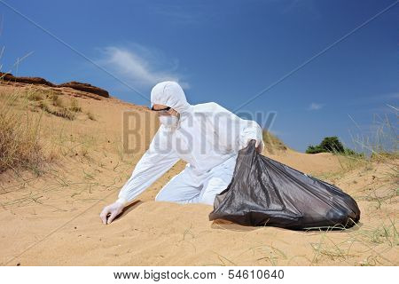 Male worker in protective suit holding a waste bag and collecting samples from sand, symbolizing pollution