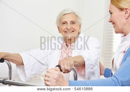 Happy senior woman sitting with geriatric nurse on her bed