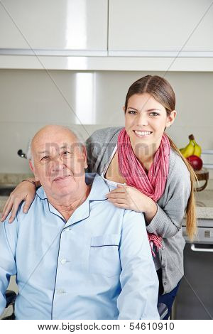 Smiling young woman with a senior man in a wheelchair