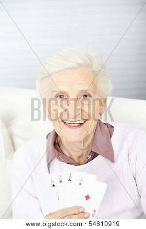 Smiling senior woman holding four aces in her hand while playing cards