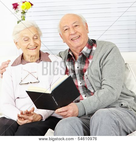 Man reading a book to senior woman at home