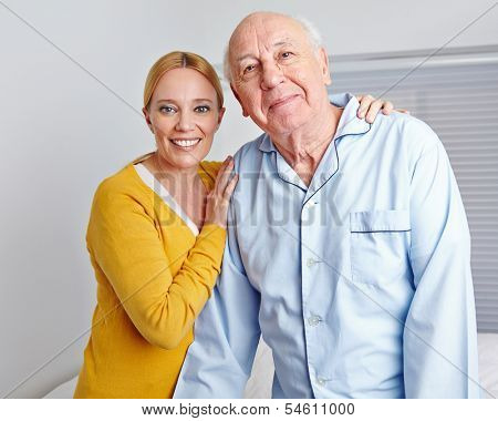 Smiling caregiver nursing senior man in family at home