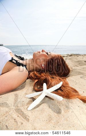 The Beautiful Girl Lies On Sea Coast With Shells