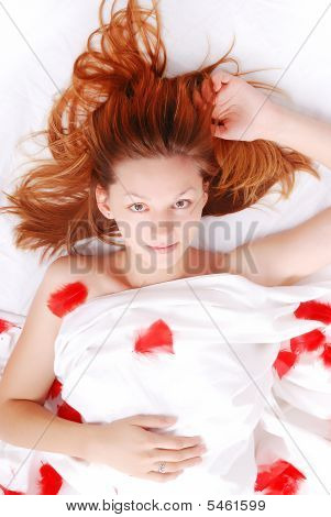Beautiful Girl In Bed With Red Plumage