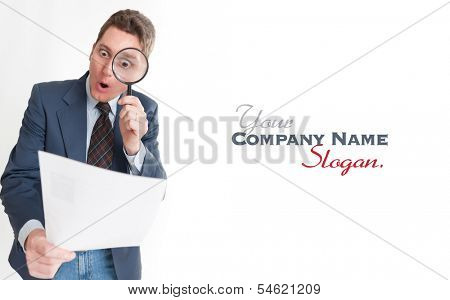 Young businessman looking to a document through a magnifying glass