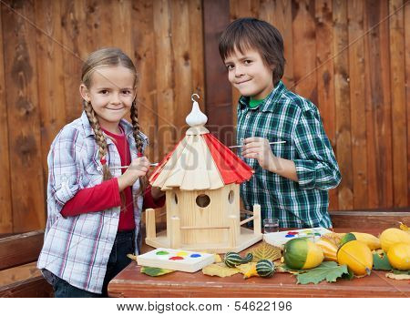 Kids painting the bird house preparing for winter - environmental awareness concept