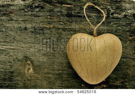 a paperboard heart-shaped ornament on an old wooden surface with a copy space