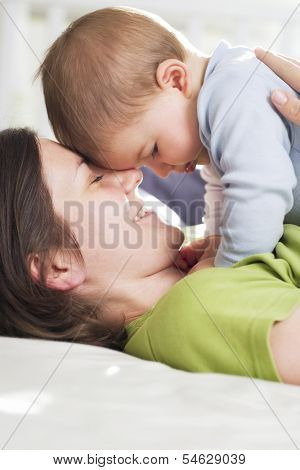 Moments of tenderness: Happy loving mother and baby boy cuddling with affection while lying down in bed.