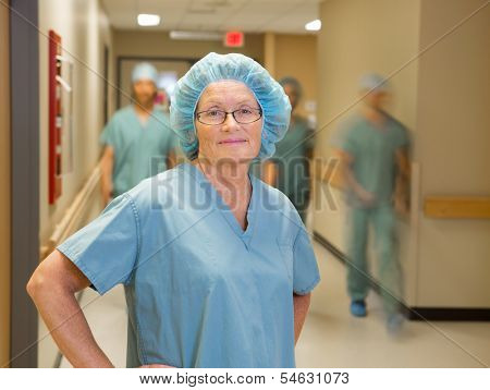 Portrait of confident female doctor with team walking in hospital corridor