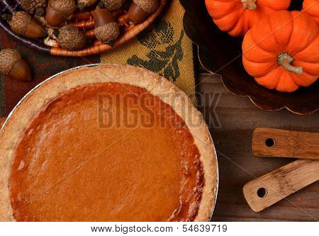 Overhead view of a fresh baked pumpkin pie ready for Thanksgiving. The pie is surrounded by autumn accessories including acorns, and mini pumpkins. Horizontal format.