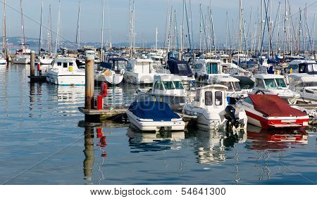 Motor boats in a marina with masts and calm blue sea