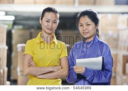 two young chinese female workers in uniform in discussing warehousing system
