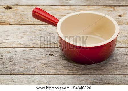 empty red stoneware soup cup on a rustic wooden table