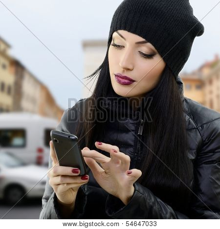 Young beautiful brunette woman touching and browsing her smart phone over city background