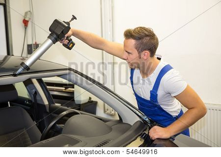 Glazier With Application Gun In Garage Replacing Windshield Or Windscreen