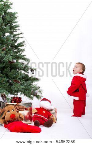Santa Baby boy standing next to Christmas tree.