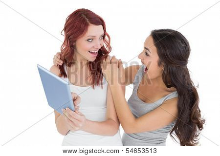 Two shocked young female friends with digital tablet against white background