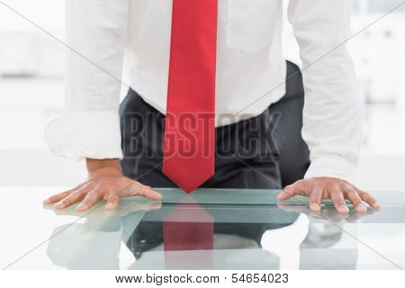 Close-up mid section of a well dressed businessman with hands on the desk at office